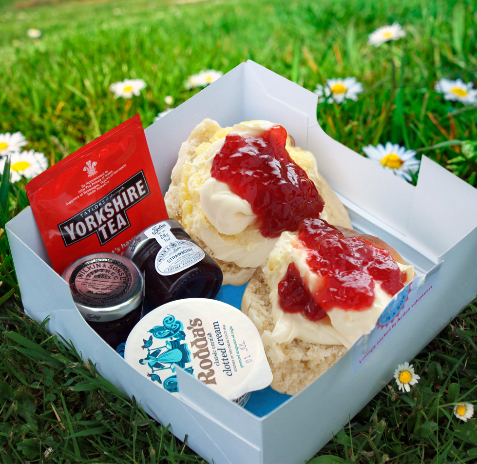 Scones with jam and cream in a box on grass