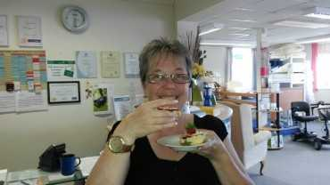 A woman smiling whilst eating a scone