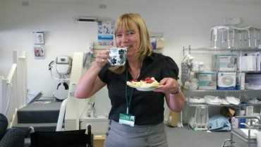 Smiling woman holding a plate with a scone and drinking from her cup of tea