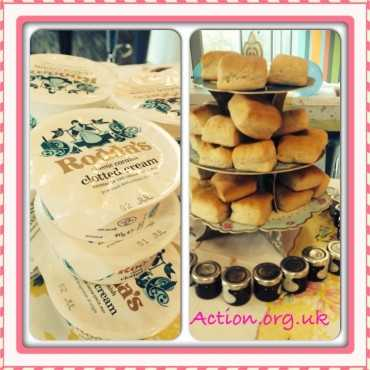 On the left side of the image a pile of many tubs of clotted cream and on the right side a cake stand piled with many scones