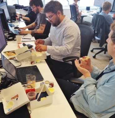 Office workers at their desks enjoying their scones