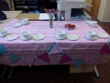 Table with a pink striped tablecloth and matching bunting laid for tea for 6