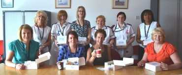 Group of medical people posing with their cream tea boxes and cups of tea