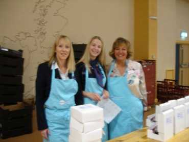 3 female volunteer cream tea box packers posing for the camera