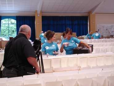 Volunteers adding jam to cream tea boxes