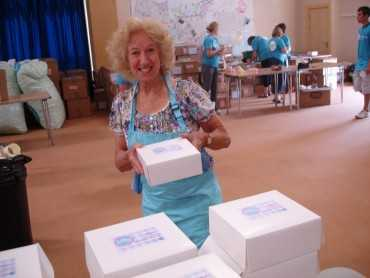 Female volunteer box packer posing with one of her full boxes