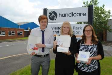 A man and 2 women by the business Handicare's sign holding their cream tea boxes