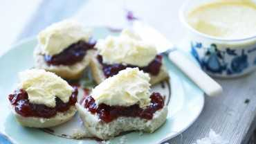 A plate with scone halves smothered in jam and cream