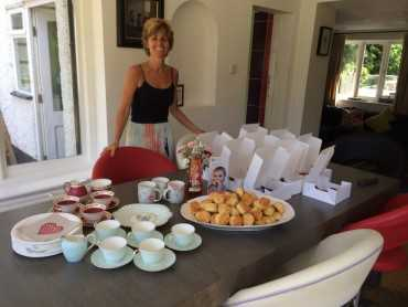 Woman behind a table full of empty tea cups and full cream tea boxes