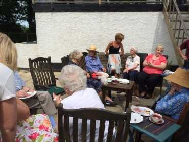 Group of women sitting outside enjoying their cream teas