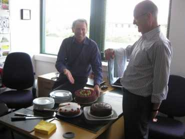 2 men in an office next to a table laden with cakes and empty plates and serviettes