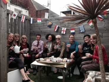 people in a back garden with cream tea boxes on a table