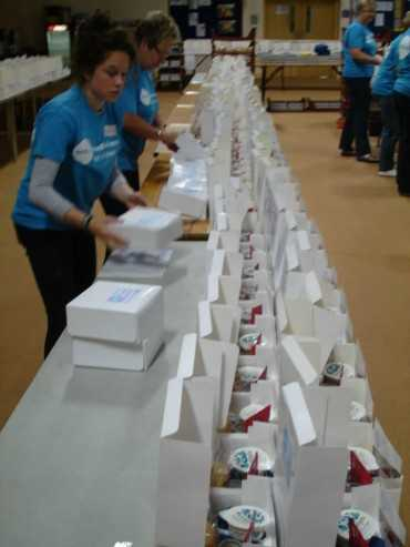 volunteers behind a long line of tables packing boxes of scones