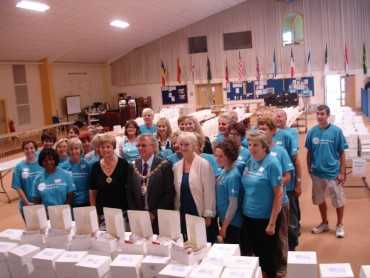 Mayor posing with the volunteer cream tea box packers behind a table full of boxes
