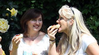 Three women enjoying scones with jam and cream
